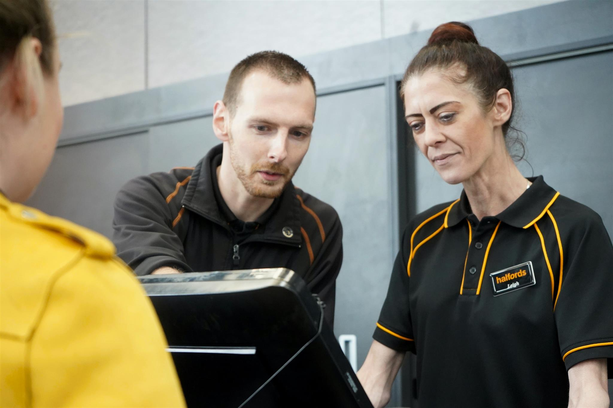 Ex-offender serving a customer in a Halfords shop.